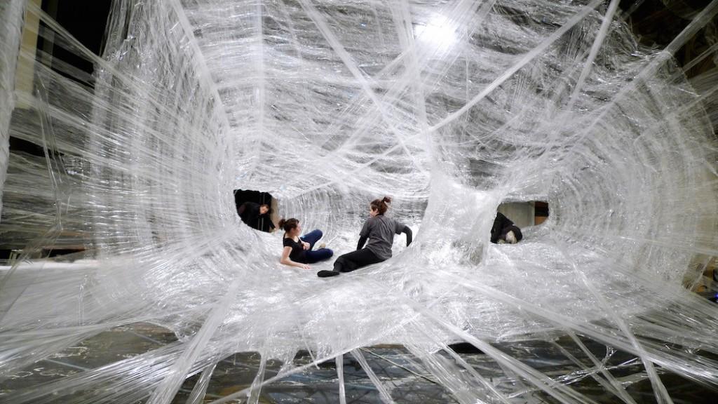 personas interactuando en instalacion tela de araña