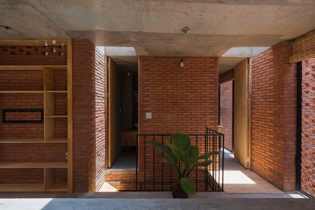 estanterías de madera que aprovechan los huecos dejados por los ladrillos y el hormigón. Tropical Space