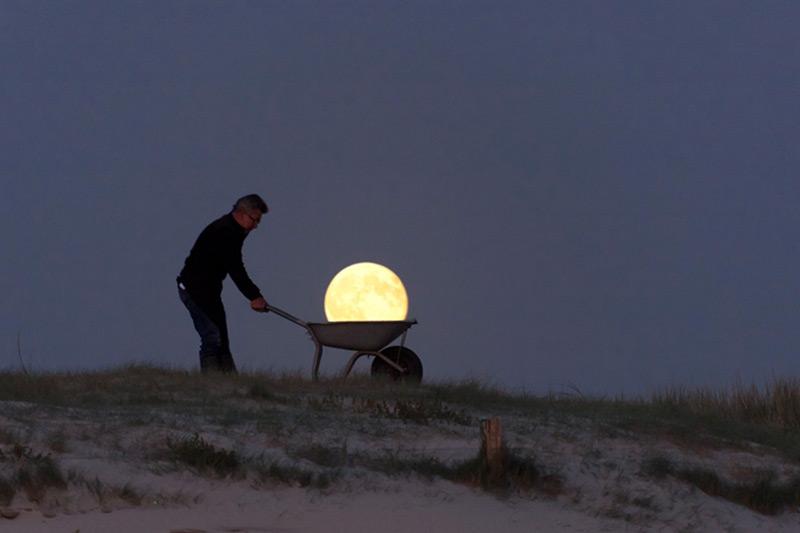 Fotografía surrealista la luna pasea en carretilla por la playa