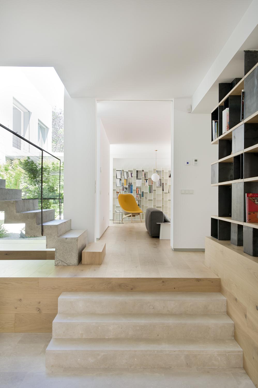 Proyecto de reforma estudio ÁBATON arquitectura. escalera de piedra y pavimento de madera. silla al fondo