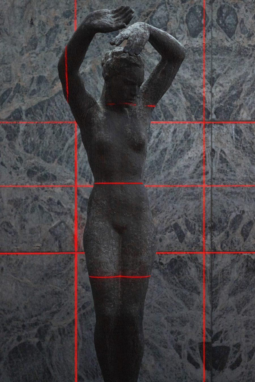 proyección de láseres rojos iluminando la escultura «Alba» de Georg Kolbe